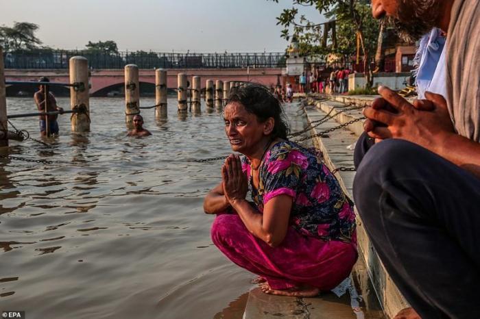 Это Рани. Ее муж Анил погиб, вычищая канализационную шахту в Нью-Дели. Рани проводит прощальный ритуал на берегу притока Ганга. Газиабад, Уттар-Прадеш демонстрация, индия, канализация, каста, неприкасаемые, протесты, социальные проблемы, уборщики