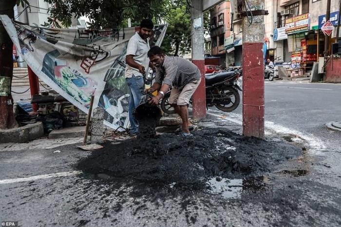 Помощники Джони опорожняют набранные им ведра демонстрация, индия, канализация, каста, неприкасаемые, протесты, социальные проблемы, уборщики