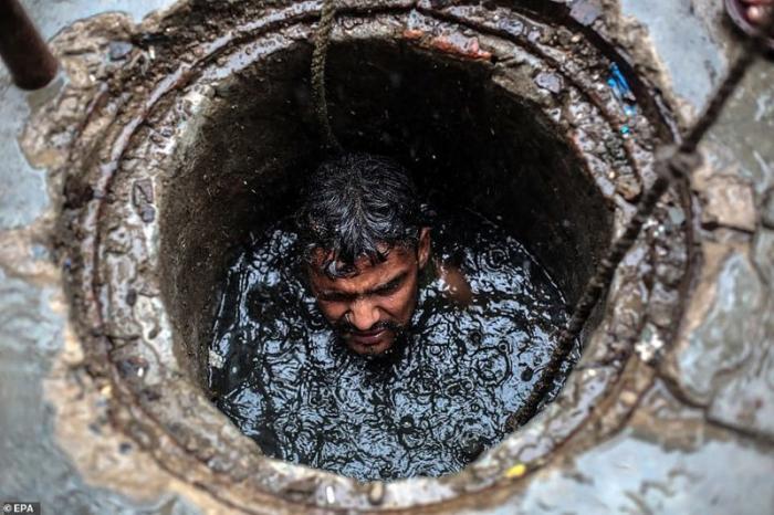 Джони, 26-летний чистильщик канализации, во время исполнения служебных обязанностей. Газиабад, штат Уттар-Прадеш, июль 2018 г. демонстрация, индия, канализация, каста, неприкасаемые, протесты, социальные проблемы, уборщики
