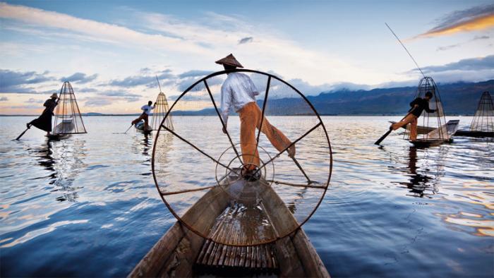 Рыбаки на рассвете. Техника рыбалки народ инта, живущего у озера Инле, со стороны напоминает необычную по почерку хореографию: в одной руке рыбаки держат сеть, а в другой — весло, которым они управляют ногой.